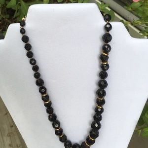 Necklace black and gold tone.